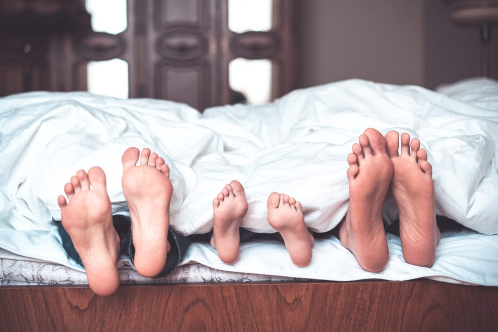 happy family of three is lying on the bed and only feet seen on the blanket